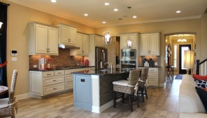 Kitchen cabinet 2 by Burrows Cabinets at Travisso with painted cabinets in Bone with black glaze on perimeter cabinets and Ash on the island