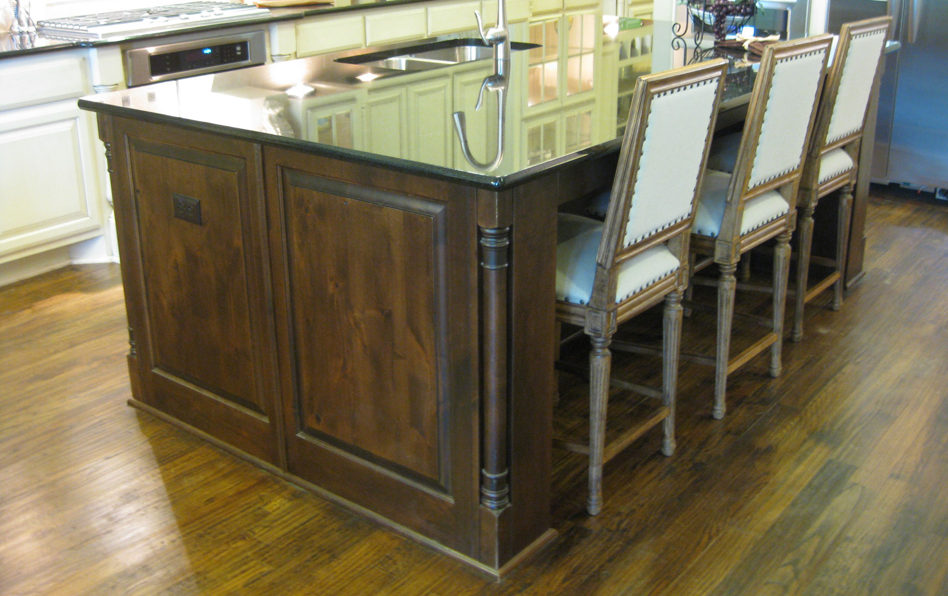 kitchen island in knotty alder with Tuscan corner posts by Burrows Cabinets and recessed seating