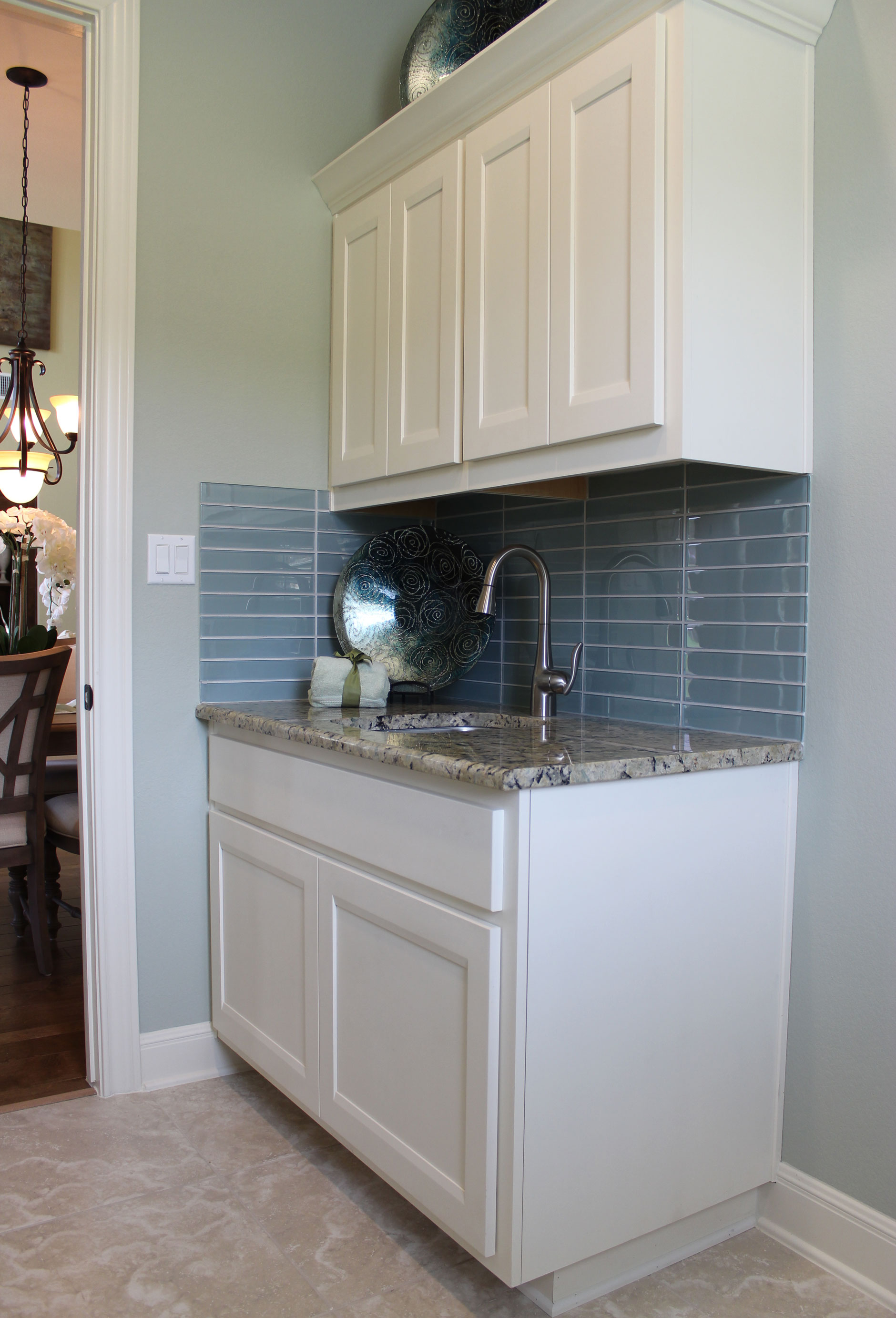 Laundry room cabinets in Bone with Briscoe doors by Burrows Cabinets