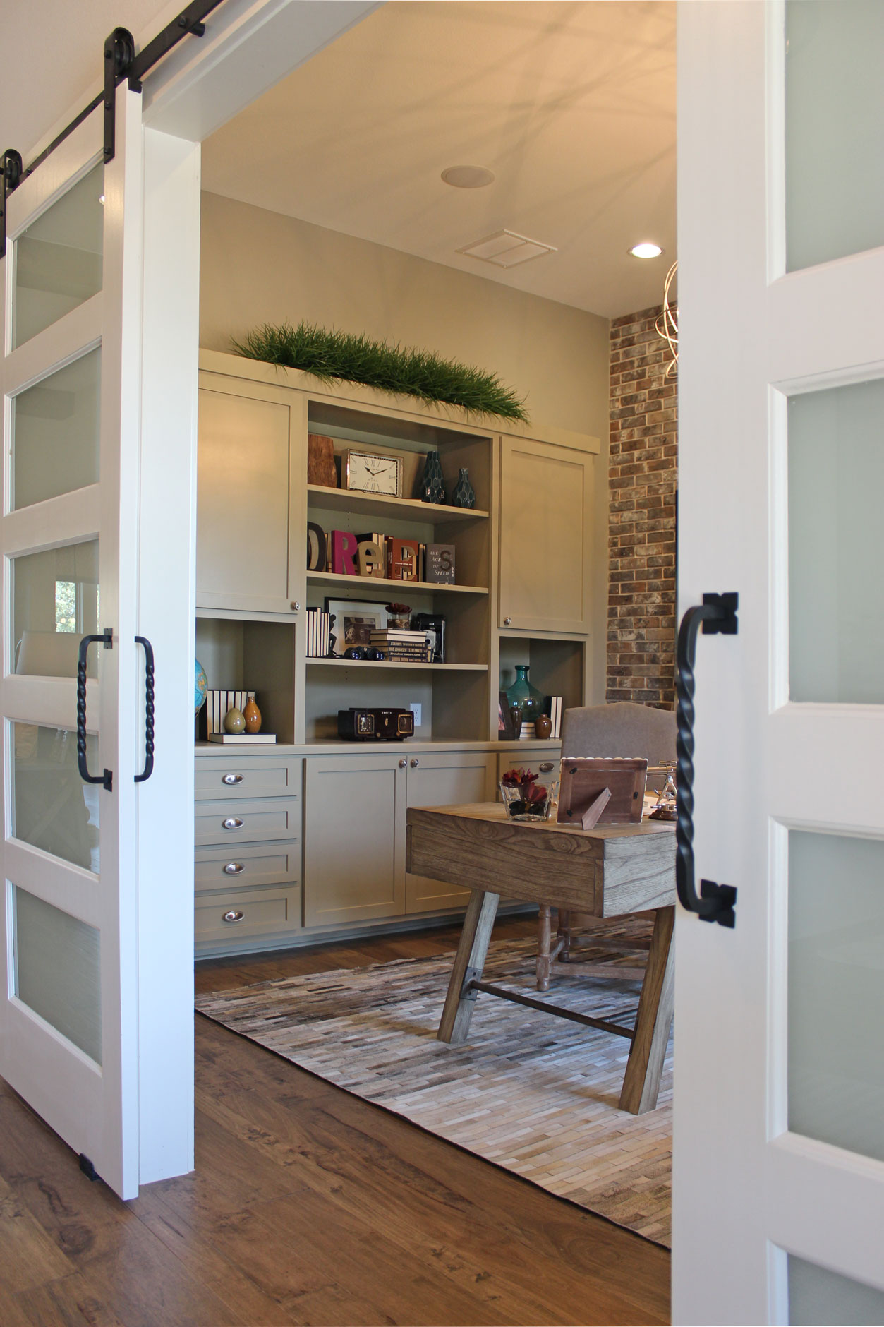 Burrows Cabinets' study with gray cabinets and sliding barn doors