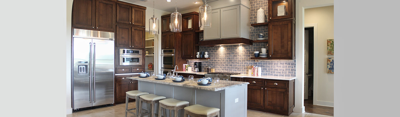 Kitchen with floating shelves and wood and gray painted cabinets by Burrows Cabinets