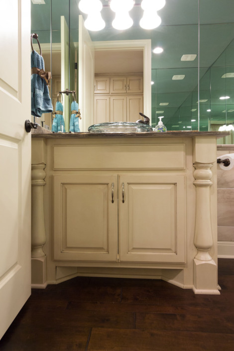 Burrows Cabinets' bathroom vanity in bone with brown glaze and Monaco half round decorative posts