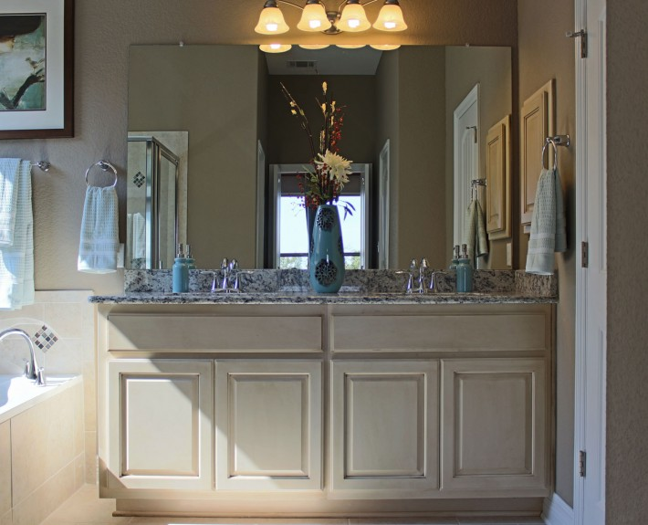 Burrows Cabinets bathroom vanity in bone with brown glaze and dual sinks