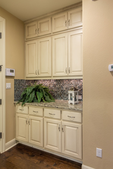 Burrows Cabinets butler's pantry cabinets in bone with brown glaze and raised panel doors