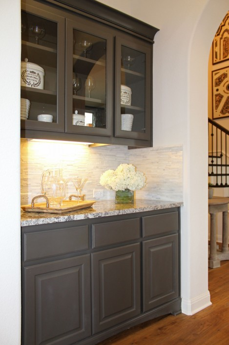 Butler's pantry with glass doors in upper cabinets in Umber gray paint