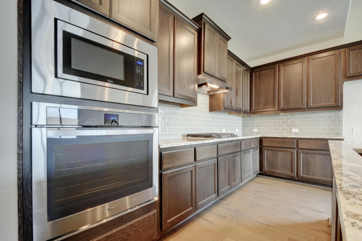 Burrows Cabinets kitchen cabinets with flat panel doors in Driftwood