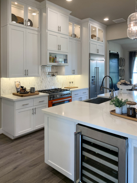 white kitchen with shaker doors and wine refrigerator in island