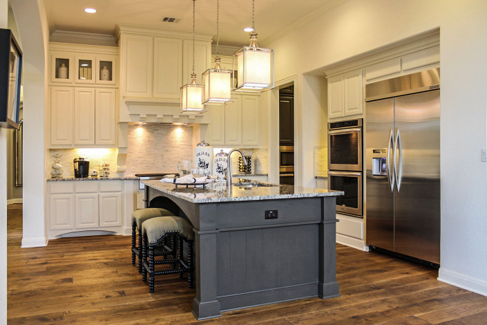 Burrows Cabinets' kitchen cabinets in bone white with custom wood vent hood and Umber gray island