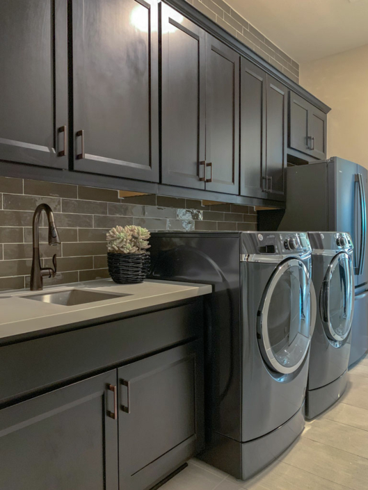 Laundry room cabinets by Burrows Cabinets in Beech Espresso with Briscoe doors