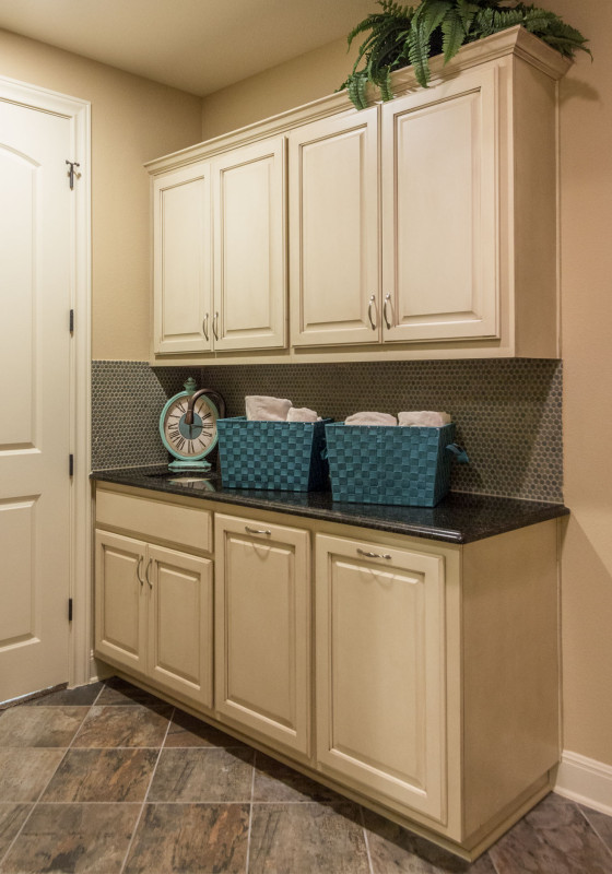 Burrows Cabinets' laundry room cabinets in bone with brown glaze
