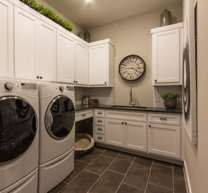 Burrows Cabinets' laundry room with shaker doors in bone white and dog bed space