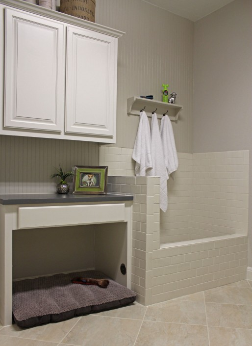Burrows Cabinets' laundry room cabinets painted white with built-in dog shower