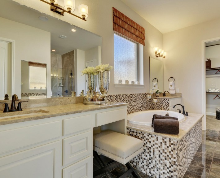 Burrows Cabinets' master bath in bone with knee space and dual vanities