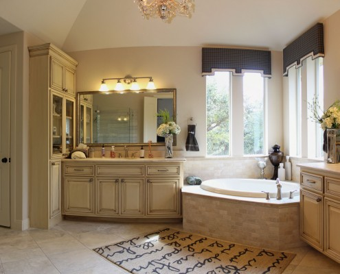 Burrows Cabinets master bath cabinets in bone with brown glaze and tall cabinet with mullioned glass doors