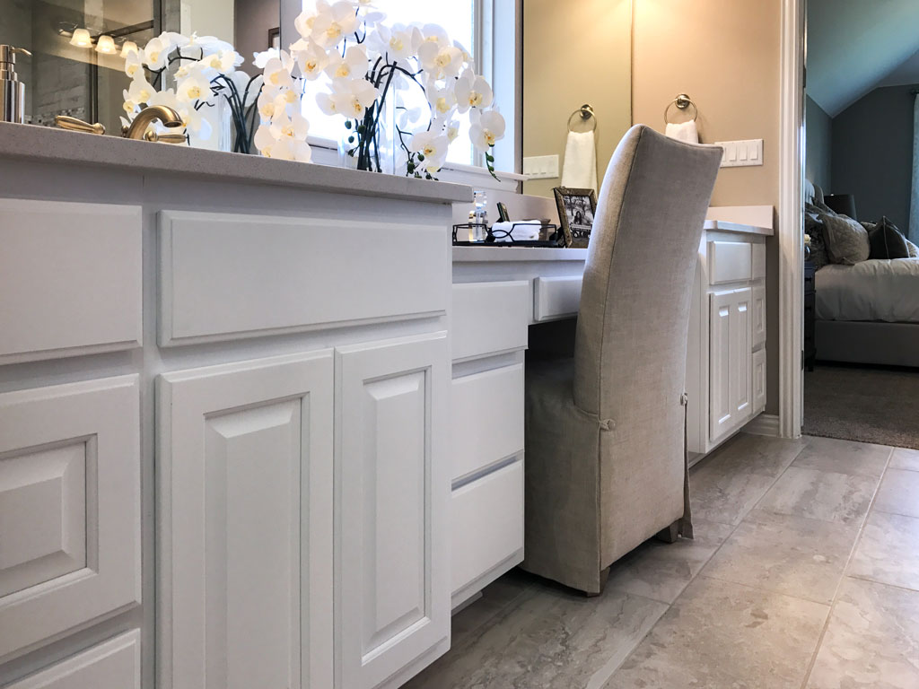 Burrows CabinetsPrimary bath cabinets with lower height sitting space and bumped out vanity