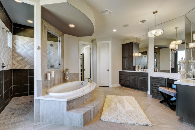 Burrows Cabinets' master bathroom cabinets with raised panel doors in Umber and doorless walk-in shower